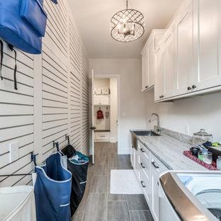 Exempel på en stor lantlig grå parallell grått tvättstuga enbart för tvätt, med en rustik diskho, skåp i shakerstil, vita skåp, granitbänkskiva, vita väggar, klinkergolv i porslin, en tvättmaskin och torktumlare bredvid varandra och grått golv