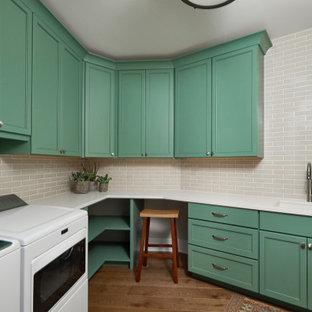 Idee per una sala lavanderia tradizionale con lavello sottopiano, ante in stile shaker, ante verdi, top in quarzo composito, pavimento in legno massello medio, lavatrice e asciugatrice affiancate, pavimento marrone e top bianco