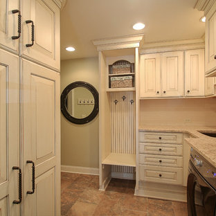 Idee per una lavanderia multiuso tradizionale di medie dimensioni con lavello sottopiano, ante con bugna sagomata, ante con finitura invecchiata, top in granito, pareti verdi e lavatrice e asciugatrice affiancate