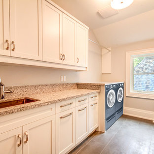 Inspiration för en stor funkis linjär tvättstuga enbart för tvätt, med en undermonterad diskho, skåp i shakerstil, vita skåp, bänkskiva i terrazo, grå väggar, klinkergolv i keramik och en tvättmaskin och torktumlare bredvid varandra