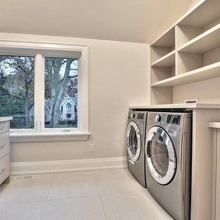Design ideas for a large scandinavian galley separated utility room in Toronto with a built-in sink, flat-panel cabinets, beige cabinets, composite countertops, beige walls, ceramic flooring, a side by side washer and dryer, beige floors and beige worktops.