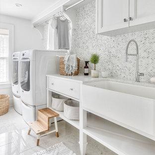 Exempel på en klassisk vita vitt tvättstuga enbart för tvätt, med en allbänk, luckor med infälld panel, vita skåp, vita väggar, en tvättmaskin och torktumlare bredvid varandra och vitt golv