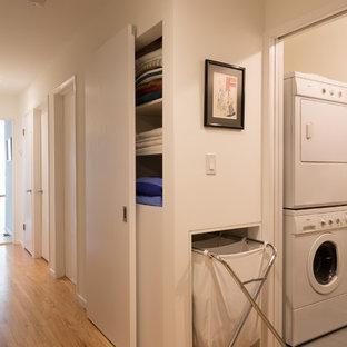 Foto di una piccola lavanderia multiuso minimalista con pareti bianche, pavimento in gres porcellanato e lavatrice e asciugatrice a colonna
