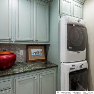 Foto di una grande lavanderia tradizionale con ante turchesi, top in quarzite, lavatrice e asciugatrice a colonna e top nero