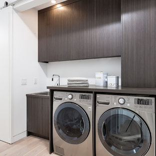 Inspiration for a contemporary single-wall utility room in Toronto with a single-bowl sink, flat-panel cabinets, dark wood cabinets, white walls, light hardwood flooring, a side by side washer and dryer and beige floors.