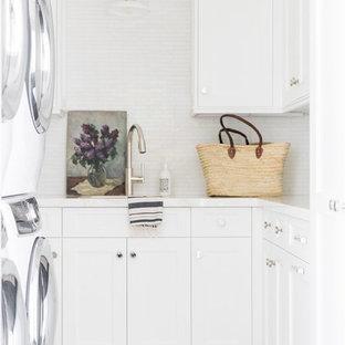 Idee per una piccola sala lavanderia costiera con top in marmo, pareti bianche, lavatrice e asciugatrice a colonna, pavimento grigio, top bianco, lavello sottopiano, ante in stile shaker e ante bianche