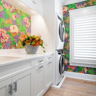 Idee per una lavanderia multiuso costiera di medie dimensioni con lavello sottopiano, ante bianche, top in quarzite, pareti multicolore, pavimento in legno massello medio, lavatrice e asciugatrice a colonna, pavimento marrone, top bianco e ante in stile shaker