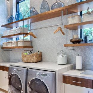 Inspiration för en funkis tvättstuga enbart för tvätt, med öppna hyllor, skåp i mellenmörkt trä och en tvättmaskin och torktumlare bredvid varandra