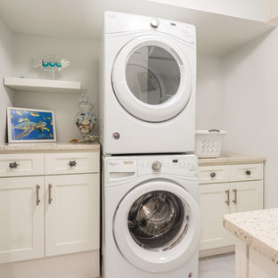 Example of a mid-sized transitional galley porcelain floor and gray floor dedicated laundry room design in Orlando with shaker cabinets, white cabinets, recycled glass countertops, gray walls, a stacked washer/dryer and multicolored countertops