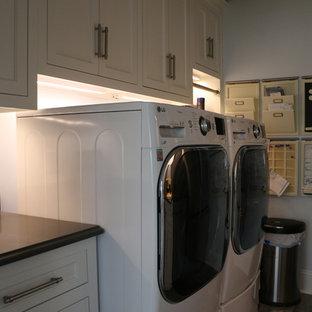 Foto di una lavanderia tropicale di medie dimensioni con lavello sottopiano, ante in stile shaker, ante bianche, pareti blu, lavatrice e asciugatrice affiancate e pavimento marrone