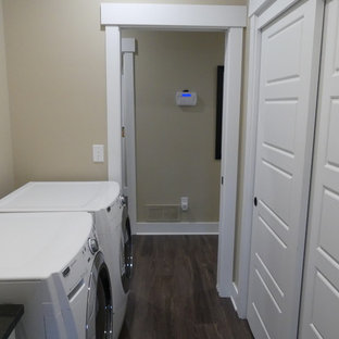 Medium sized traditional galley separated utility room in Columbus with a built-in sink, recessed-panel cabinets, white cabinets, laminate countertops, beige walls, medium hardwood flooring, a side by side washer and dryer, brown floors and black worktops.