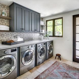 Idéer för mellanstora medelhavsstil linjära grått tvättstugor enbart för tvätt, med luckor med upphöjd panel, grå skåp, bänkskiva i kvarts, vita väggar, travertin golv, en tvättmaskin och torktumlare bredvid varandra och beiget golv