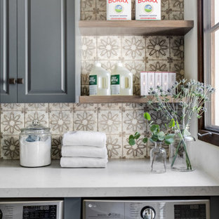 Inspiration for a mid-sized mediterranean single-wall travertine floor and beige floor dedicated laundry room remodel in Orange County with raised-panel cabinets, gray cabinets, quartz countertops, white walls, a side-by-side washer/dryer and gray countertops