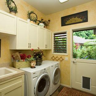 Inspiration för en mellanstor vintage linjär tvättstuga enbart för tvätt, med en nedsänkt diskho, skåp i shakerstil, vita skåp, kaklad bänkskiva, gula väggar, betonggolv och en tvättmaskin och torktumlare bredvid varandra