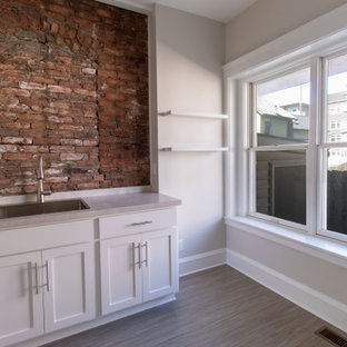 Large eclectic dedicated laundry room in Cleveland with shaker cabinets, white cabinets, laminate benchtops, red splashback, brick splashback, beige walls, porcelain floors, beige floor and beige benchtop.