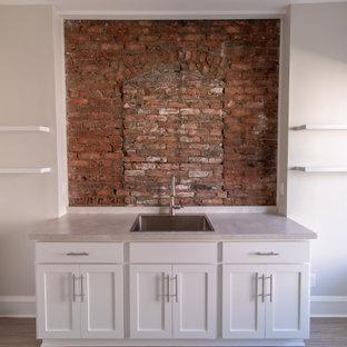 Foto på en stor eklektisk beige tvättstuga enbart för tvätt, med skåp i shakerstil, vita skåp, laminatbänkskiva, rött stänkskydd, stänkskydd i tegel, beige väggar, klinkergolv i porslin och beiget golv