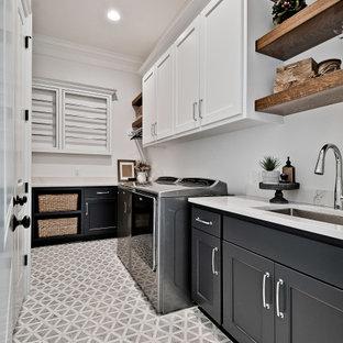 Exempel på en stor amerikansk vita parallell vitt tvättstuga enbart för tvätt, med en undermonterad diskho, luckor med upphöjd panel, vita skåp, bänkskiva i kvartsit, vitt stänkskydd, vita väggar, klinkergolv i porslin, en tvättmaskin och torktumlare bredvid varandra och grått golv