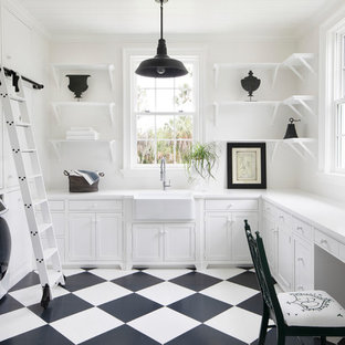 Inspiration for a large transitional u-shaped white floor utility room remodel in Tampa with a farmhouse sink, shaker cabinets, white cabinets, white walls, a side-by-side washer/dryer and white countertops