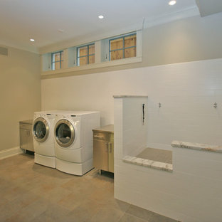 Example of a large classic single-wall ceramic tile utility room design in Chicago with flat-panel cabinets, gray cabinets, stainless steel countertops, gray walls and a side-by-side washer/dryer