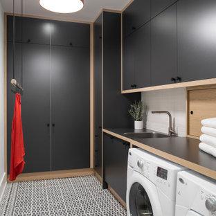 Bild på en funkis svarta linjär svart tvättstuga, med en undermonterad diskho, släta luckor, svarta skåp, vita väggar, en tvättmaskin och torktumlare bredvid varandra och flerfärgat golv