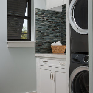 Inspiration for a beach style light wood floor and beige floor dedicated laundry room remodel in Miami with shaker cabinets, white cabinets, blue walls, a stacked washer/dryer and beige countertops