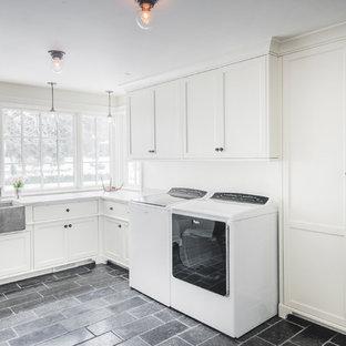 Exempel på ett stort klassiskt vit parallellt vitt grovkök, med en rustik diskho, släta luckor, vita skåp, granitbänkskiva, vita väggar, en tvättmaskin och torktumlare bredvid varandra, betonggolv och grått golv