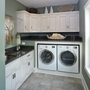 Inspiration for a traditional utility room in Cleveland with green walls, white cabinets, grey floors and black worktops.
