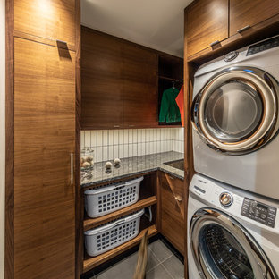 This is an example of a small modern l-shaped separated utility room in Cedar Rapids with a built-in sink, flat-panel cabinets, dark wood cabinets, granite worktops, white walls, porcelain flooring, a stacked washer and dryer, grey floors and black worktops.