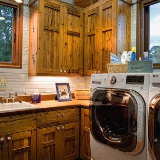 Inspiration för mellanstora rustika l-formade tvättstugor enbart för tvätt, med en nedsänkt diskho, luckor med upphöjd panel, skåp i mellenmörkt trä, en tvättmaskin och torktumlare bredvid varandra och vita väggar