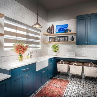 Klassisk inredning av ett stort vit u-format vitt grovkök, med en undermonterad diskho, blå skåp, bänkskiva i kvarts, klinkergolv i keramik, en tvättmaskin och torktumlare bredvid varandra, vitt golv, luckor med infälld panel och grå väggar