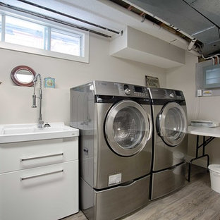 Mid-sized urban single-wall dark wood floor dedicated laundry room photo in Calgary with an utility sink, flat-panel cabinets, white cabinets, white walls and a side-by-side washer/dryer