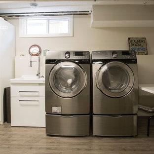 Immagine di una sala lavanderia industriale di medie dimensioni con lavatoio, ante lisce, pareti bianche, parquet scuro, lavatrice e asciugatrice affiancate e pavimento marrone
