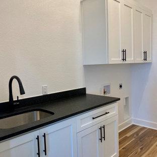 Exempel på en stor lantlig svarta parallell svart tvättstuga enbart för tvätt, med en undermonterad diskho, skåp i shakerstil, vita skåp, granitbänkskiva, svart stänkskydd, vita väggar, laminatgolv, en tvättmaskin och torktumlare bredvid varandra och brunt golv