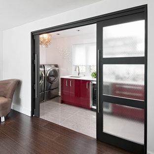 Aménagement d'une buanderie contemporaine avec des portes de placard rouges, un mur blanc, un sol gris et un plan de travail blanc.