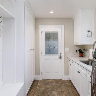 Idéer för att renovera en mellanstor vintage vita parallell vitt tvättstuga enbart för tvätt, med en undermonterad diskho, skåp i shakerstil, vita skåp, bänkskiva i kvarts, vitt stänkskydd, beige väggar, klinkergolv i porslin, en tvättmaskin och torktumlare bredvid varandra och brunt golv