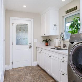 Foto på en mellanstor vintage vita parallell tvättstuga enbart för tvätt, med en undermonterad diskho, skåp i shakerstil, vita skåp, bänkskiva i kvarts, vitt stänkskydd, beige väggar, klinkergolv i porslin, en tvättmaskin och torktumlare bredvid varandra och brunt golv
