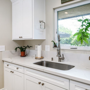 Photo of a mid-sized traditional galley dedicated laundry room in Sacramento with an undermount sink, shaker cabinets, white cabinets, quartz benchtops, white splashback, beige walls, porcelain floors, a side-by-side washer and dryer, brown floor, white benchtop and wood.