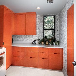 Inredning av en modern mellanstor tvättstuga enbart för tvätt, med släta luckor, orange skåp, flerfärgade väggar och vitt golv