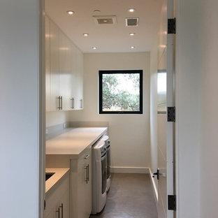 Ispirazione per un'ampia sala lavanderia contemporanea con lavello sottopiano, ante lisce, ante bianche, top in cemento, pareti bianche, pavimento in cemento, lavatrice e asciugatrice affiancate, pavimento grigio e top beige
