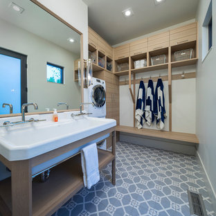 Photo of a transitional utility room in Salt Lake City with a stacked washer and dryer, blue floor and a drop-in sink.