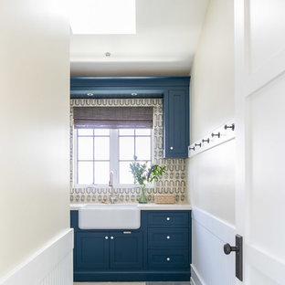 Idee per una grande sala lavanderia tropicale con lavello stile country, ante in stile shaker, ante blu, lavatrice e asciugatrice affiancate, pavimento grigio, top beige e pareti beige