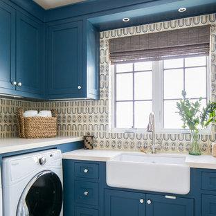 Idee per una grande sala lavanderia tropicale con lavello stile country, ante in stile shaker, ante blu, pareti multicolore, lavatrice e asciugatrice affiancate, pavimento grigio e top beige