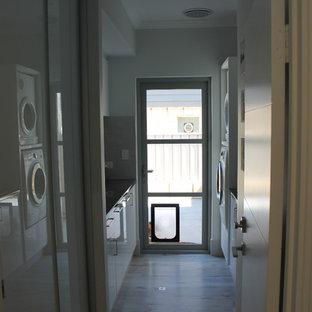 Aménagement d'une petit buanderie parallèle classique dédiée avec un placard à porte affleurante, des portes de placard blanches, un mur gris, un sol en bois peint, des machines superposées, un sol gris et un plan de travail noir.
