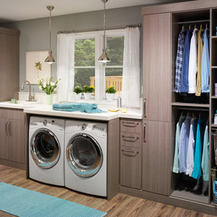 Inspiration for a large transitional single-wall laminate floor dedicated laundry room remodel in Charleston with a drop-in sink, flat-panel cabinets, brown cabinets, solid surface countertops, gray walls and a side-by-side washer/dryer