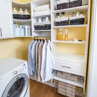 Idéer för att renovera en mellanstor l-formad tvättstuga, med luckor med upphöjd panel, vita skåp, gula väggar, bambugolv och en tvättmaskin och torktumlare bredvid varandra