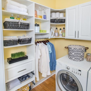 Photo of a mid-sized l-shaped laundry room in Cincinnati with raised-panel cabinets, white cabinets, yellow walls, bamboo floors and a side-by-side washer and dryer.