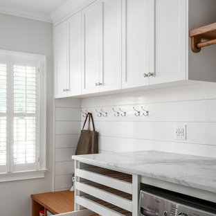 Inspiration for a mid-sized timeless ceramic tile, multicolored floor and shiplap wall utility room remodel in Atlanta with shaker cabinets, white cabinets, marble countertops, white countertops and white walls