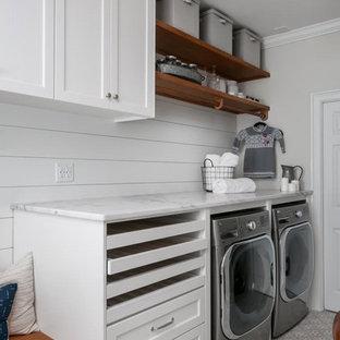 Неиссякаемый источник вдохновения для домашнего уюта: прямая универсальная комната среднего размера в классическом стиле с одинарной раковиной, фасадами в стиле шейкер, белыми фасадами, мраморной столешницей, серыми стенами, полом из керамической плитки, со стиральной и сушильной машиной рядом, серым полом и белой столешницей