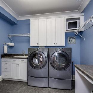 Пример оригинального дизайна: большая отдельная прачечная в стиле кантри с одинарной раковиной, фасадами с декоративным кантом, белыми фасадами, столешницей из ламината, синими стенами, полом из керамогранита и со стиральной и сушильной машиной рядом