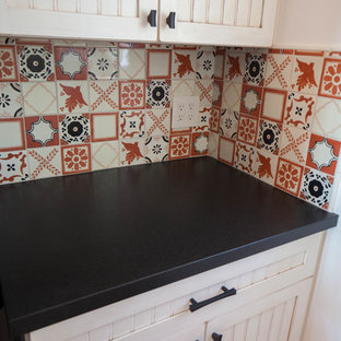 This is an example of a small eclectic galley separated utility room in San Luis Obispo with recessed-panel cabinets, beige cabinets, granite worktops, beige walls, porcelain flooring, a stacked washer and dryer, brown floors and black worktops.